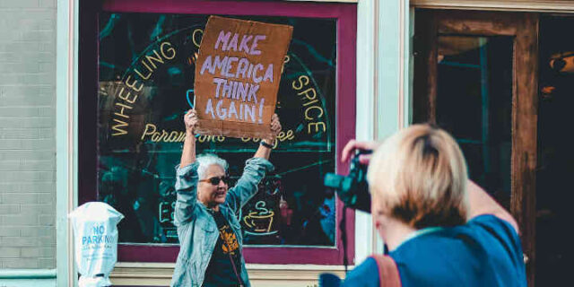 Woman holding sign - make America think again